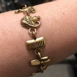 Gold tone bracelet with many charm pieces